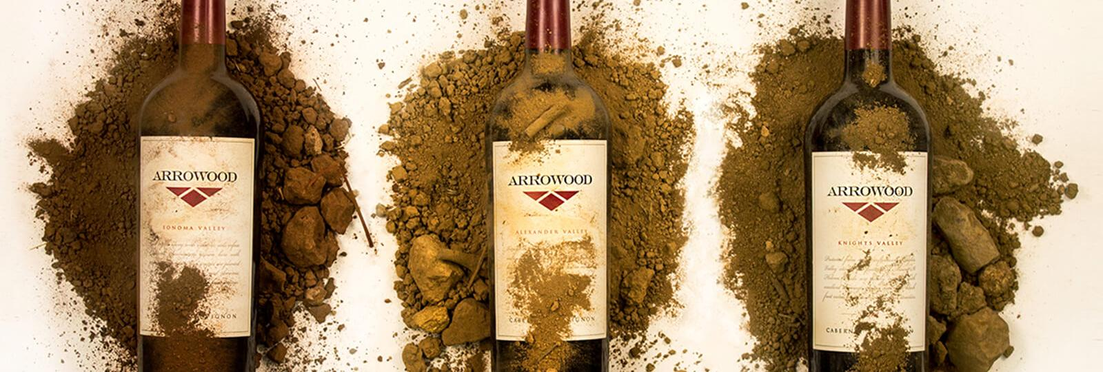 Arrowood bottles of wine with different types of dirt covering them