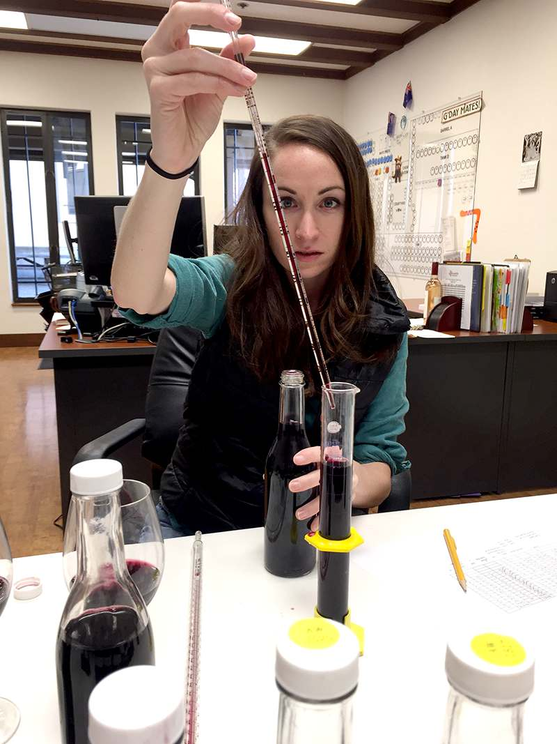Kristina carefully measures each grape variety to ensure an accurate blend composition.